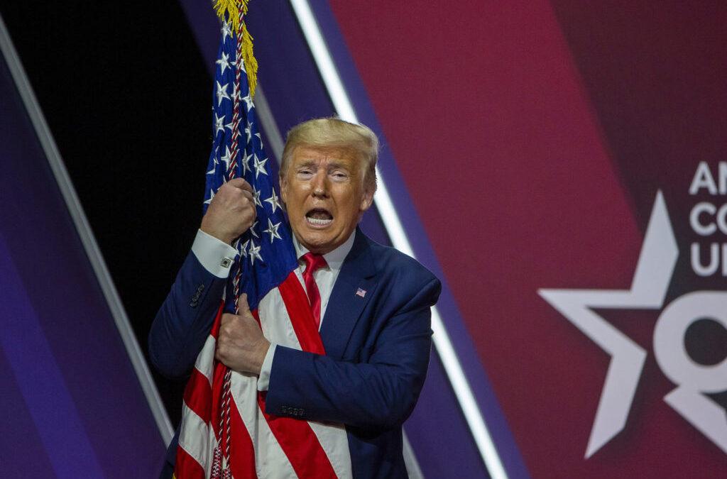 Donald Trump abrazando la bandera de los Estados Unidos de América